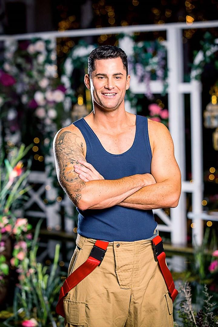 Bachelor In Paradise season three cast member Jamie Doran wearing a blue singlet and firefighter's trousers