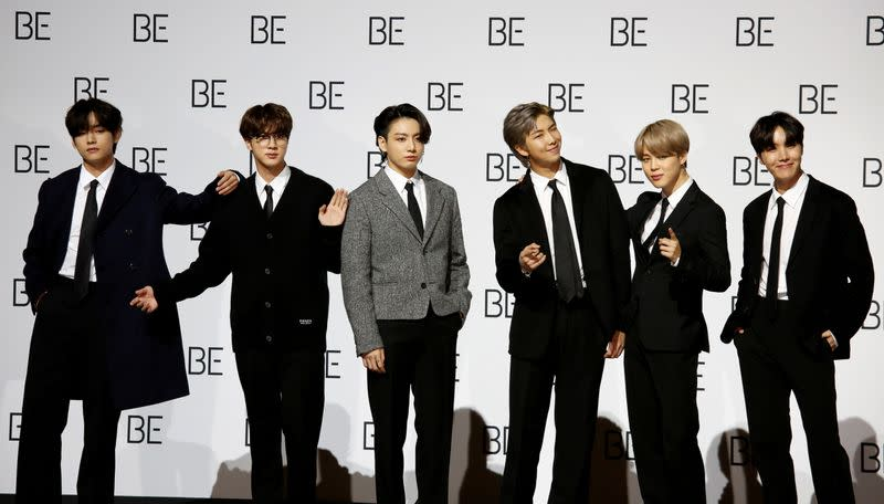 """Members of K-pop boy band BTS pose for photographs during a news conference promoting their new album """"BE(Deluxe Edition)"""" in Seoul"""