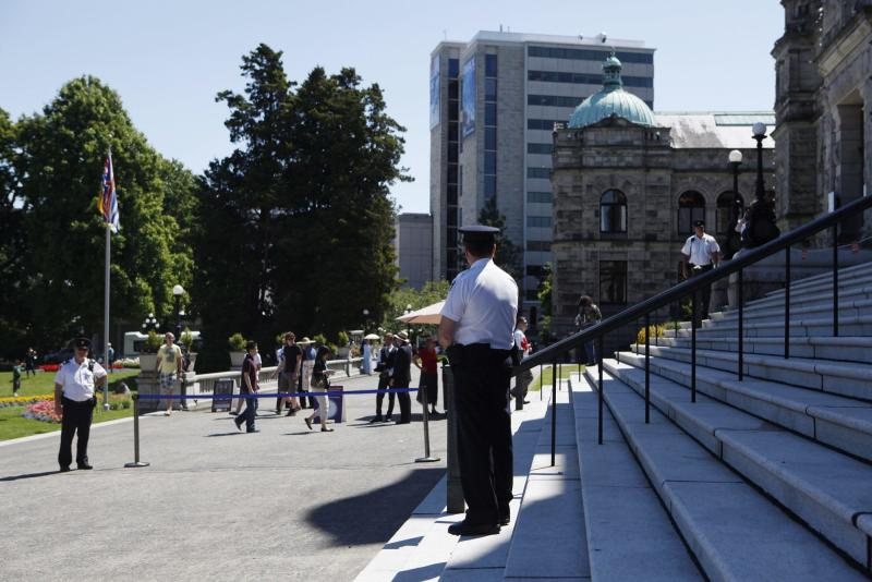 Security guards watch over the legislature grounds in Victoria,B.C., Tuesday, July 2, 2013. Police have arrested a Canadian man and a woman and charged them as terrorist suspects for attempting to leave a suspicious package at British Columbia's provincial legislature on Canada Day. Royal Canadian Mounted Police Asst. Com James Malitzia says John Stewart Nuttall and Amanda Marie Korody were arrested Monday. The pair has been charged with conspiracy, facilitating a terrorist activity and making an explosive device. (AP Photo/The Canadian Press, Chad Hipolito)