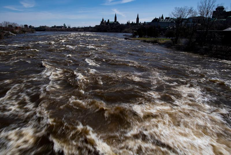 Parliament Hill and the Ottawa skyline are seen as the Ottawa River churns underneath Portage Bridge, which connects Ottawa and Gatineau, on Sunday, April 28, 2019. Rising water levels have contributed to flooding on both sides of the river. (Justin Tang/The Canadian Press via AP)