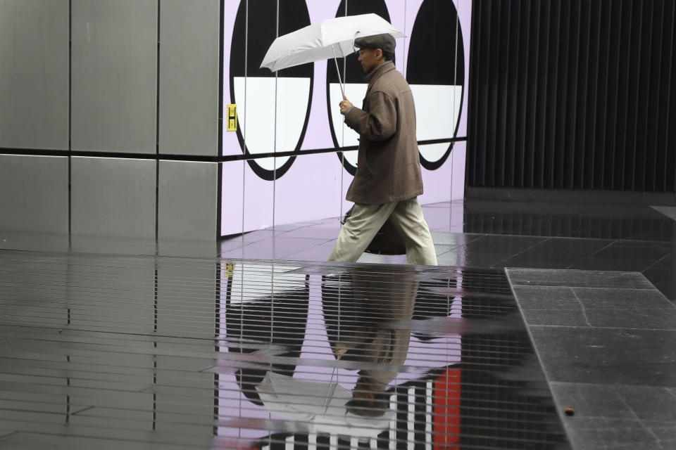 A man is reflected in a puddle as he passes part of a public artwork by French artist Camille Walala in London, Tuesday, Oct. 27, 2020. The British government is sticking to its strategy of tiered, regional restrictions to combat COVID-19 amid mounting political and scientific pressure for stronger nationwide measures to prevent the pandemic from spiralling out of control. (AP Photo/Kirsty Wigglesworth)