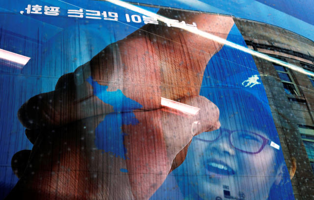 A girl smiles from behind the reflection of a large banner adorning the exterior of City Hall ahead of the upcoming summit between North and South Korea in Seoul, South Korea April 25, 2018. REUTERS/Jorge Silva TPX IMAGES OF THE DAY