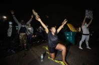 A woman who was tear gassed while confronting police raises her arms after police allegedly shot and killed a man, in Brooklyn Center, Minnesota