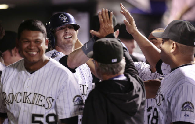 Colorado Rockies' Wilton Lopez, right, smiles as Charlie Blackmon, middle, high fives teammates after scoring against the PIttsburgh Pirates in the sixth inning of a baseball game in Denver on Saturday, Aug. 10, 2013. Colorado beat Pittsburgh 6-4.(AP Photo/Joe Mahoney)