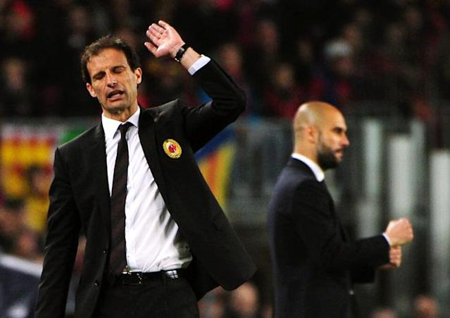 AC Milan's coach Massimiliano Allegri and Barcelona's coach Josep Guardiola (background) react during the Champions League quarter-final second leg football match FC Barcelona vs AC Milan on April 3, 2012 at Camp Nou stadium in Barcelona. AFP PHOTO / OLIVIER MORIN