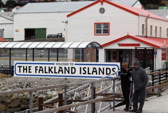 "Argentine Falklands War veterans Hugo Romero (R) and Walter Sarverry walk next to a ""Welcome to the Falkland Islands"" sign in Port Stanley, in this picture taken March 14, 2012."
