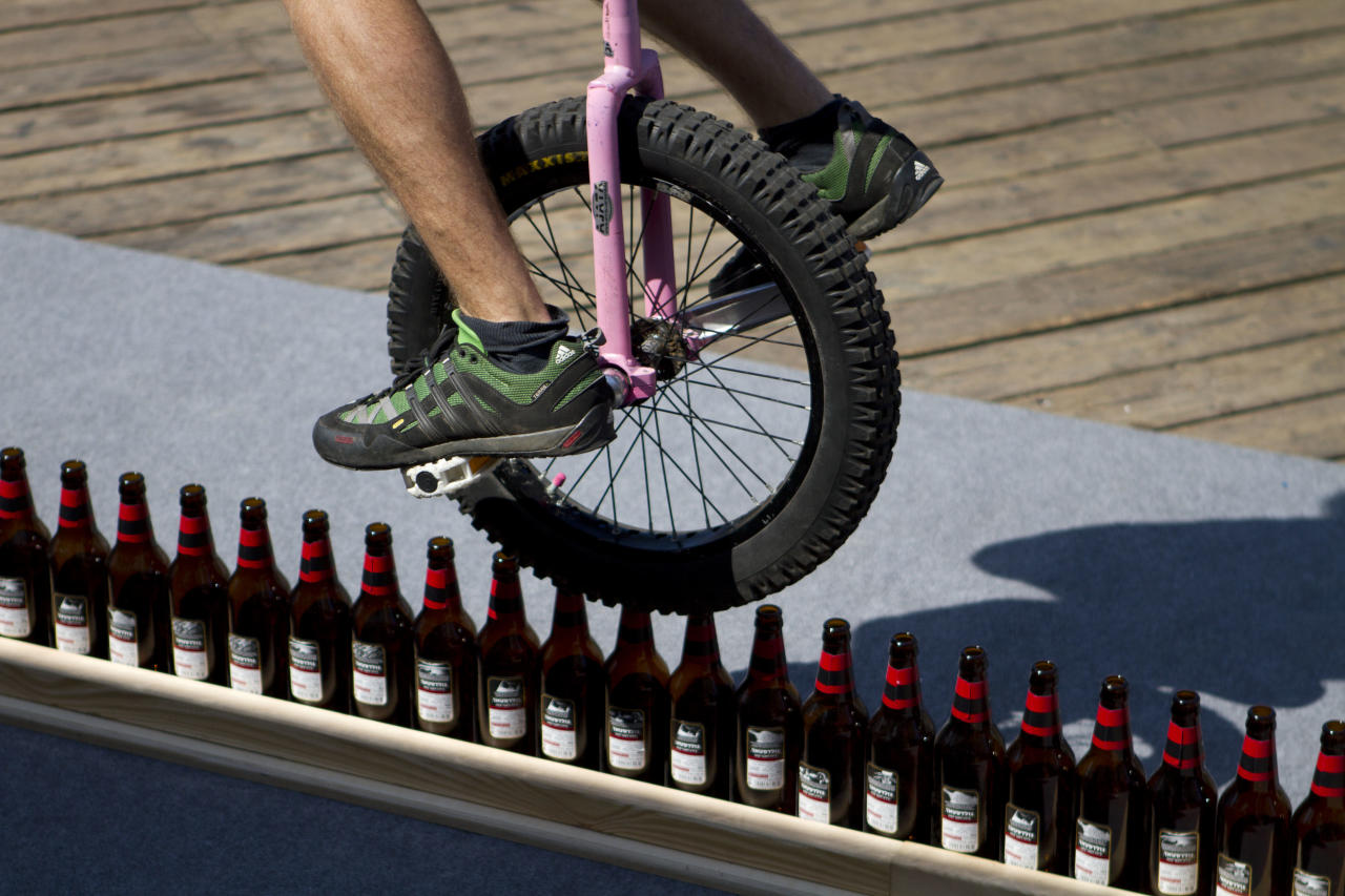 German unicycle rider Lutz Eichholz rides over beer bottles as he attempts to break his existing Guinness World record Monday, Sept. 26, 2011 in Tel Aviv, Israel. Eichholz rode his unicycle 8.93 meters over 127 beer bottles on Monday and is waiting for verification on this latest attempt . (AP Photo/Ariel Schalit)