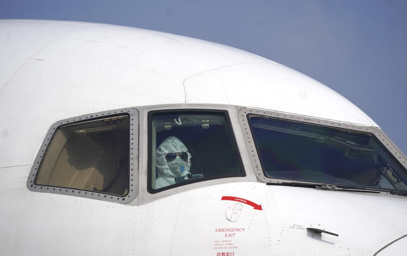 In this photo released by China's Xinhua News Agency, a pilot wearing a protective suit parks a cargo plane at Wuhan Tianhe International Airport in Wuhan in central China's Hubei Province, Tuesday, Jan. 28, 2020. Hong Kong's leader announced Tuesday that all rail links to mainland China will be cut starting Friday as fears grow about the spread of a new virus. (Cheng Min/Xinhua via AP)