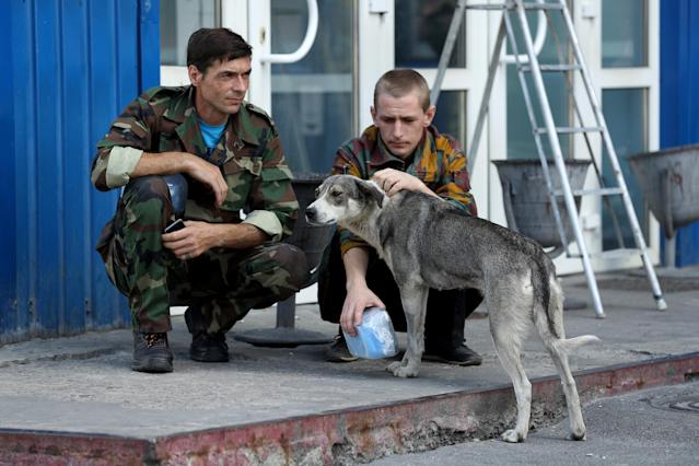 <p>Workers on a break pet a stray dog they have named Bulka outside an administrative building inside the exclusion zone at the Chernobyl nuclear power plant on Aug. 18, 2017, near Chernobyl, Ukraine. (Photo: Sean Gallup/Getty Images) </p>