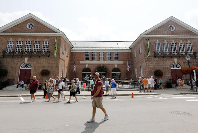Fans walk outside the Baseball Hall of Fame and Museum on Friday, July 25, 2014, in Cooperstown, N.Y. Former Major League Baseball managers Joe Torre, Bobby Cox and Tony La Russa, with pitchers Greg Maddux and Tom Glavine and slugger Frank Thomas, will be inducted to the hall on Sunday. (AP Photo)
