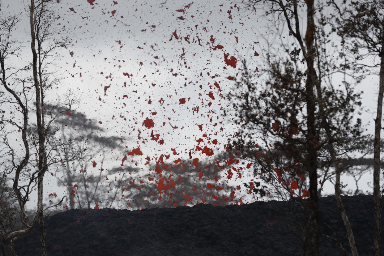 <em>Lava shoot out of a fissure on Pohoiki Rd, near Pahoa, Hawaii, where residents had to cover their faces with masks after a volcano exploded, sending a mixture of pulverised rock, glass and crystal into the air (Picture: AP)</em>