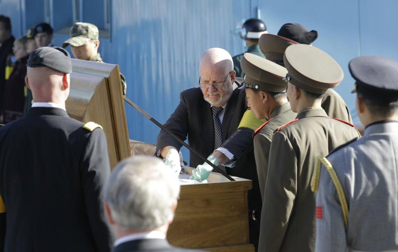 North Korean soldiers and a United Nations Command officer inspect the body of a North Korean soldier who, inside a coffin, was found dead in September in the South Korea's Hantan River during the repatriation ceremony at the border village of the Panmunjom (DMZ) that separates the two Koreas since the Korean War, north of Seoul, South Korea, Wednesday, Nov. 3, 2010. (AP Photo/ Lee Jin-man)