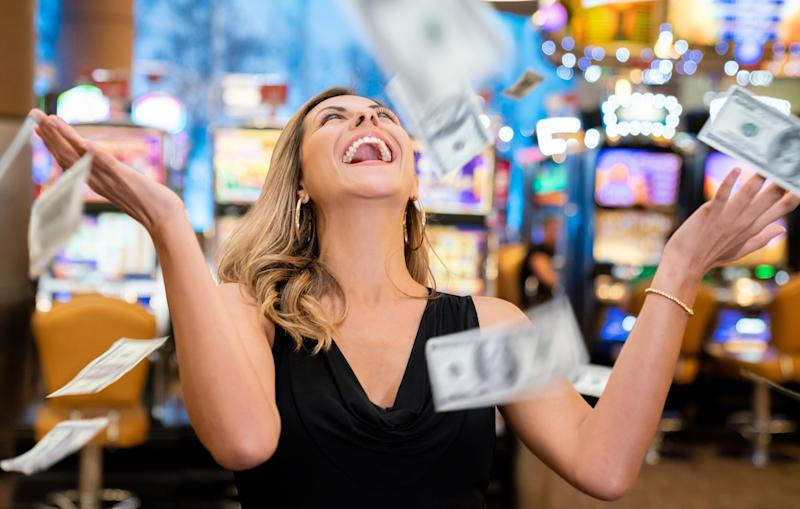 Cheerful beautiful woman excited about all the money she won at the casino throwing to the air very happy