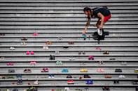 <p>Lorelei Williams places one of 215 pairs of children's shoes on the steps of the Vancouver Art Gallery as a memorial to the 215 children whose remains have been found buried at the site of a former residential school in Kamloops, in Vancouver, on Friday, May 28, 2021. Chief Rosanne Casimir of the Tk'emlups te Secwépemc First Nation said in a news release Thursday that the remains were confirmed last weekend with the help of a ground-penetrating radar specialist. THE CANADIAN PRESS/Darryl Dyck</p>