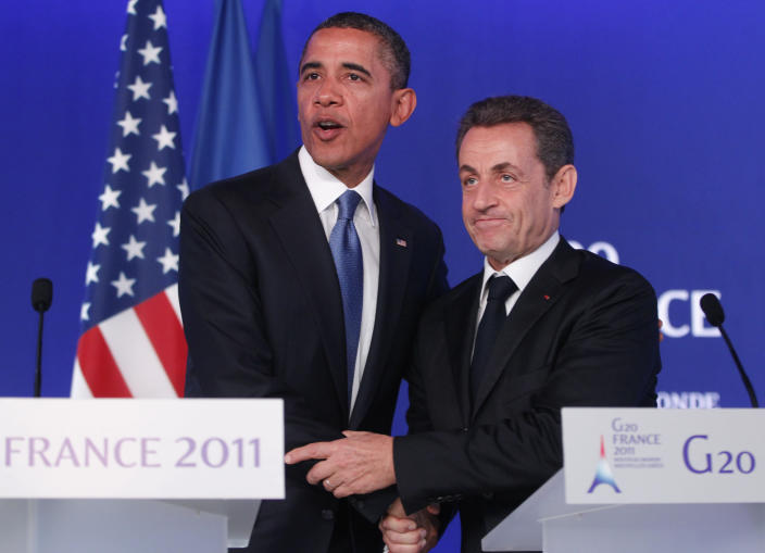 FILE - In this Nov.3, 2011 file photo, U.S. President Barack Obama, left, and French President Nicolas Sarkozy shake hands after they made statements to reporters after their meeting at the G20 Summit in Cannes, southern France. A Paris court on Monday found French former President Nicolas Sarkozy guilty of corruption and influence peddling and sentenced him to one year in prison and a two-year suspended sentence. The 66-year-old politician, who was president from 2007 to 2012, was convicted for having tried to illegally obtain information from a senior magistrate in 2014 about a legal action in which he was involved.(AP Photo/Charles Dharapak, File)