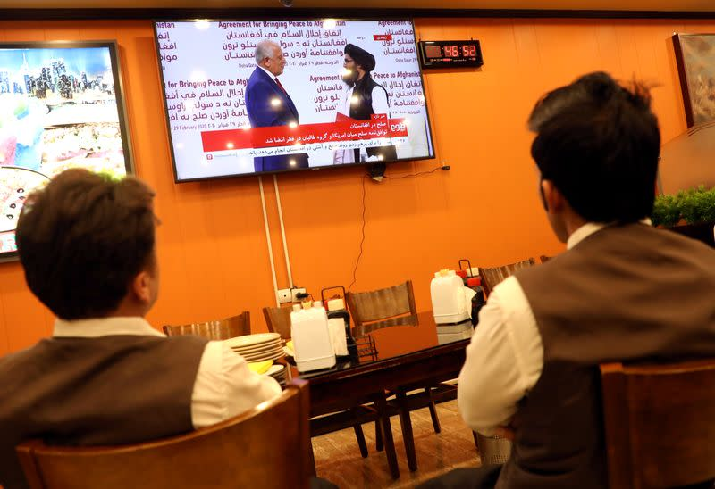FILE PHOTO: Afghans watch a live TV broadcast at a restaurant during an agreement signing ceremony between the U.S. and the Taliban in Kabul