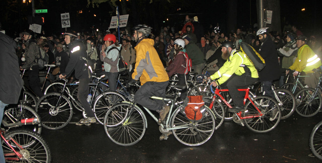 Protesters ride around the Occupy Portland Camp in Portland, Ore., Sunday, Nov. 13, 2011. The city set a 12:01 a.m. deadline for protesters to vacate but backed down after thousands of protesters showed up. (AP Photo/Don Ryan)