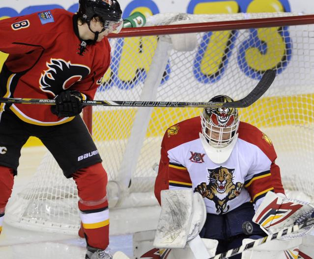 Florida Panthers goalie Tim Thomas, right, makes a save as Calgary Flames' Joe Colborne looks for the rebound during the second period of an NHL hockey game, Friday, Nov. 22, 2012 in Calgary, Alberta. (AP Photo/The Canadian Press, Larry MacDougal)