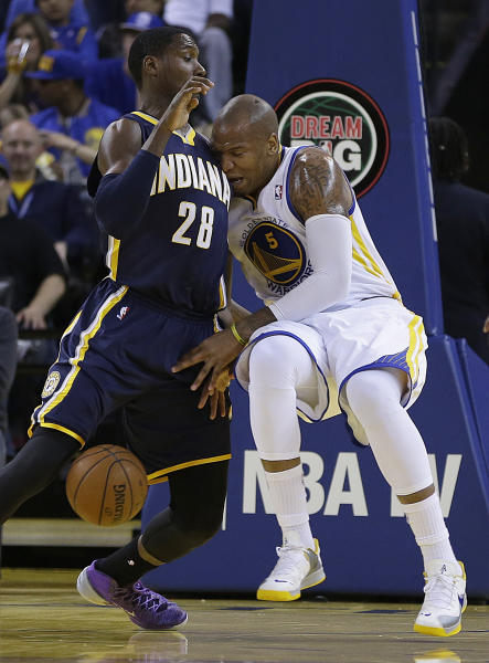 Golden State Warriors' Marreese Speights, right, loses the ball as he runs into Indiana Pacers' Ian Mahinmi (28) during the first half of an NBA basketball game, Monday, Jan. 20, 2014, in Oakland, Calif. (AP Photo/Ben Margot)