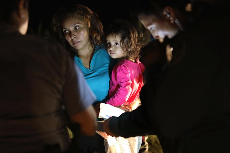 A Honduran mother holds her 2-year-old as U.S. Border Patrol agents review their papers near the U.S.-Mexico border on June 12 in McAllen, Texas. (John Moore via Getty Images)