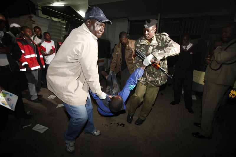 Kenyan police carry a man killed in a blast near a bus station in Nairobi, Kenya, Saturday, March 10, 2012. Explosions at one of the Kenyan capital's main bus terminals killed and injured a number of people Saturday, officials said. (AP Photo/Sayyid Azim)