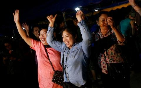 People waiting outside the caves are seen celebrating after the rescue mission was successful - Credit: AP Photo/Sakchai Lalit