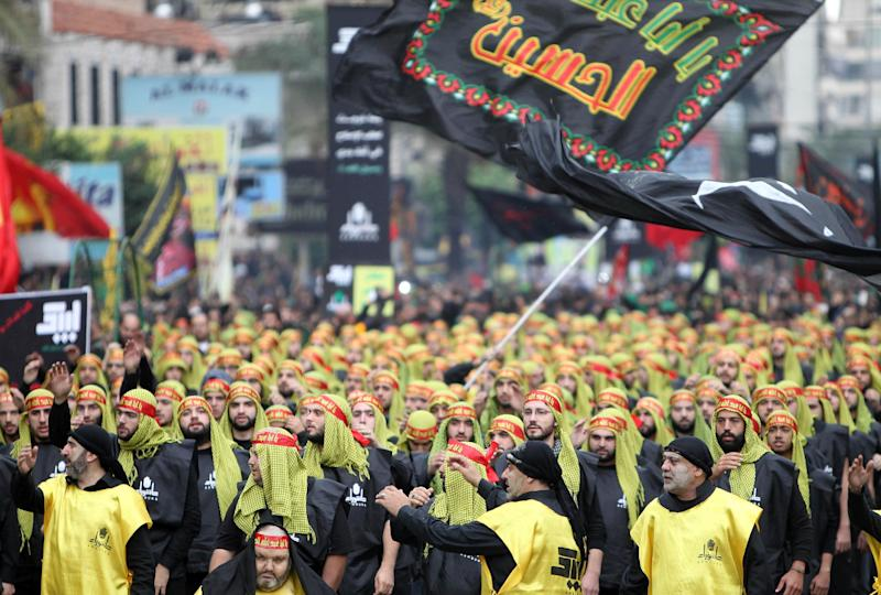 Supporters of Lebanon's Hezbollah movement take part in a parade on November 4, 2014 in Beirut's southern suburbs, where Mohammad Shawraba lived