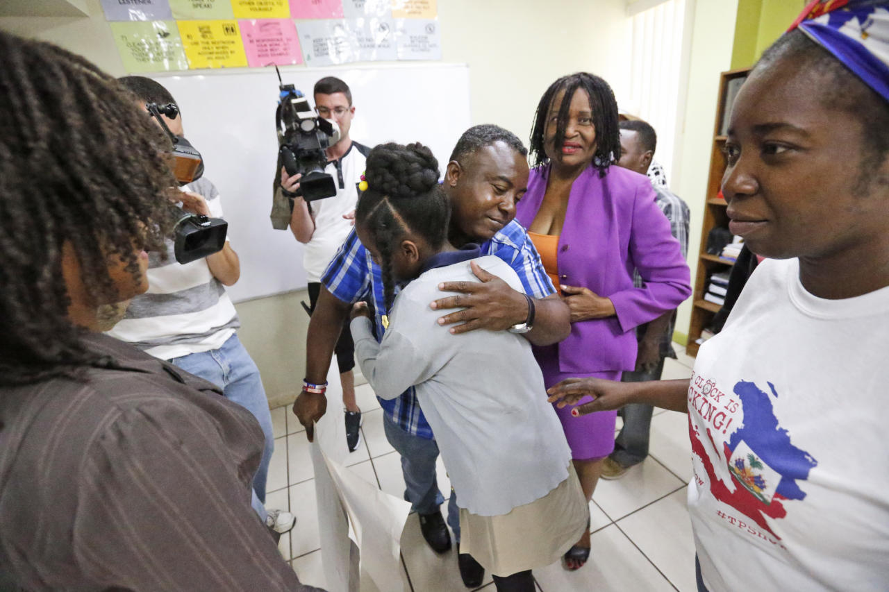 FILE - In this May 22, 2017, file photo, Pierrot Mervilier, center rear, hugs a girl that did not wish to be identified, living in the U.S. with Temporary Protected Status (TPS) after she and her family spoke to members of the media in Miami. The Trump administration said Nov. 20 it is ending a temporary residency permit program that has allowed almost 60,000 citizens from Haiti to live and work in the United States since a 2010 powerful earthquake shook the Caribbean nation. The Homeland Security Department said conditions in Haiti have improved significantly, so the benefit will be extended one last time — until July 2019 — to give Haitians time to prepare to return home. (AP Photo/Wilfredo Lee)