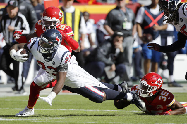 Houston Texans running back Carlos Hyde (23) is held back by Kansas City Chiefs cornerback Charvarius Ward (35) and cornerback Kendall Fuller, rear, during the second half of an NFL football game in Kansas City, Mo., Sunday, Oct. 13, 2019. (AP Photo/Colin E. Braley)