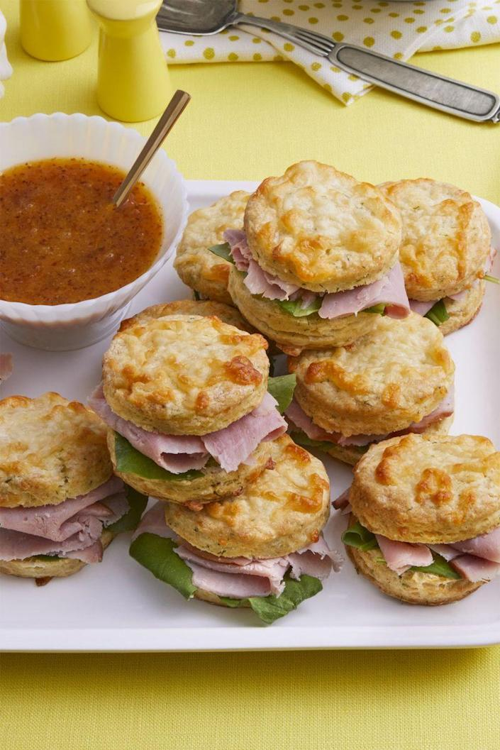 """<p>This Southern classic that sandwiches ham slices between freshly baked biscuits will be a bit hit with your brunch crowd </p><p><strong><a href=""""https://www.womansday.com/food-recipes/food-drinks/a19094239/ham-biscuits-recipe/"""" rel=""""nofollow noopener"""" target=""""_blank"""" data-ylk=""""slk:Get the Ham Biscuits recipe."""" class=""""link rapid-noclick-resp""""><em>Get the Ham Biscuits recipe.</em></a></strong></p>"""