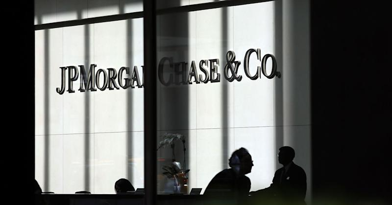 People pass a sign for JPMorgan Chase at it's headquarters in Manhattan, New York City.