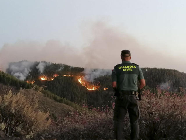 In this photo issued by the Guardia Civil, an officer looks at a forest fire in Gran Canaria, Spain, on Saturday Aug. 11, 2019. Spanish authorities say a wildfire on the Canary Island of Gran Canaria has burned 1,000 hectares (2,470 acres) and has forced the evacuation of 1,000 residents. (Guardia Civil Via AP)