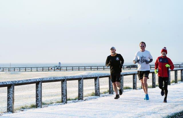 Runners were not deterred by the light snowfall on the North East coast (Owen Humphreys/PA)