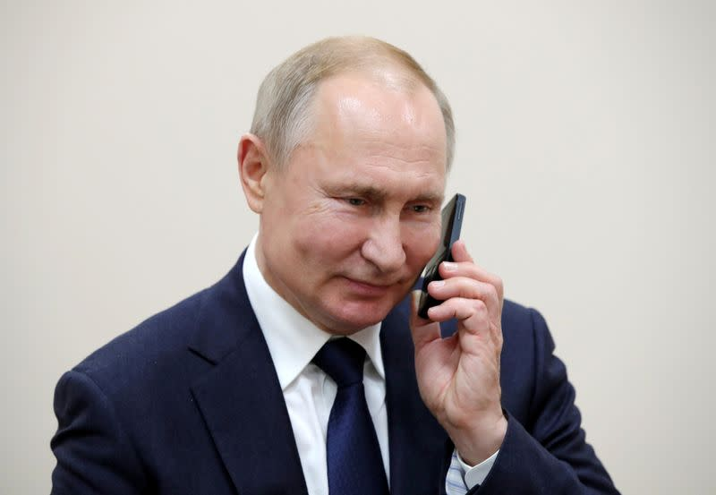 FILE PHOTO: Russian President Vladimir Putin talks on the phone in the settlement of Enem