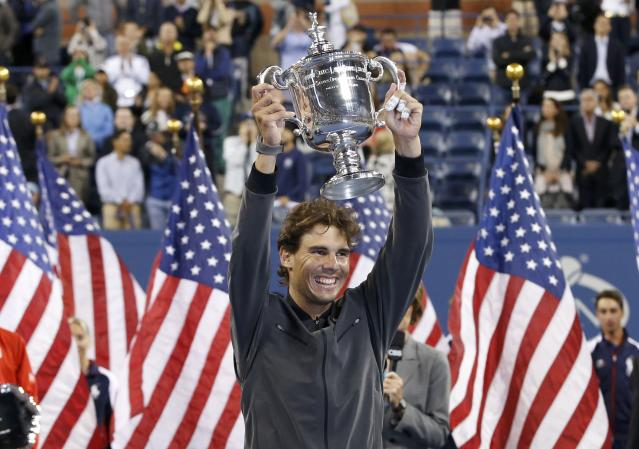 Rafael Nadal of Spain raises his trophy after defeating Novak Djokovic of Serbia in their men's final match at the U.S. Open tennis championships in New York, September 9, 2013. REUTERS/Mike Segar (UNITED STATES - Tags: SPORT TENNIS TPX IMAGES OF THE DAY)