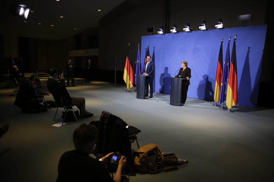 German Chancellor Angela Merkel, right, and Health Minister Jens Spahn brief the media after a virtual meeting with federal state governors at the chancellery in Berlin, Germany, Tuesday, March 30, 2021. German health officials agreed Tuesday to restrict the use of AstraZeneca's coronavirus vaccine in people under 60 amid fresh concern over unusual blood clots reported from those who received the shots. (AP Photo/Markus Schreiber, pool)