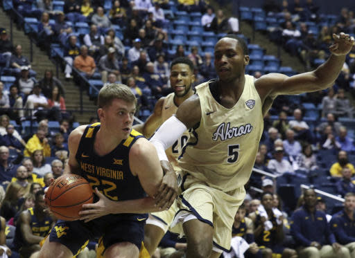 West Virginia's Sean McNeil is defended by Akron's Camron Reese during the second half of an NCAA college basketball game, Friday, Nov. 8, 2019, in Morgantown, W.Va. (AP Photo/Kathleen Batten)