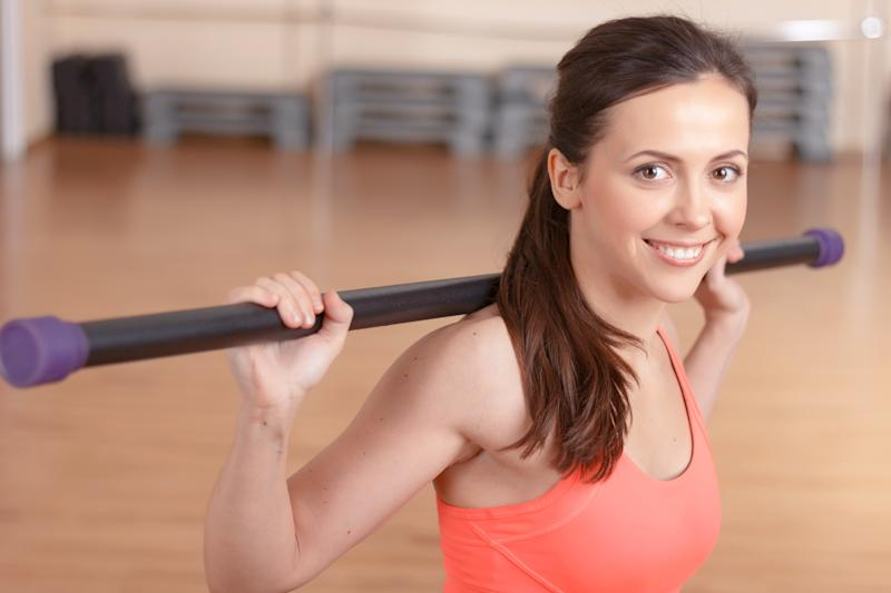 Various exercises. Portrait of smiling young woman doing stick exercises in gym.