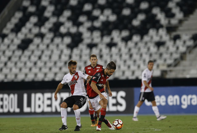 Diego of Brazil's Flamengo, right, fights for the ball with Marcelo Josemir Saracchi of Argentina's River Plate, in front of an empty stadium, during a Copa Libertadores soccer match in Rio de Janeiro, Brazil, Wednesday, Feb. 28, 2018. The South American football federation has ordered Flamengo to play two matches in an empty stadium as punishment for the bad behavior of their fans during the Copa Sudamericana Final match against Argentina's Independent last year. (AP Photo/Leo Correa)