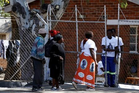 Mourners wait to pay their respects outside former Zimbabwean President Robert Mugabe's home at his rural village in Kutama