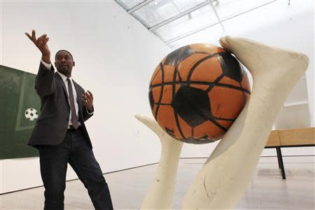"Curator Sirmans gestures near ""Free Throw"" by Caroll during construction of the exhibition, ""Futbol: The Beautiful Game"", at the Los Angeles County Museum of Art in Los Angeles"