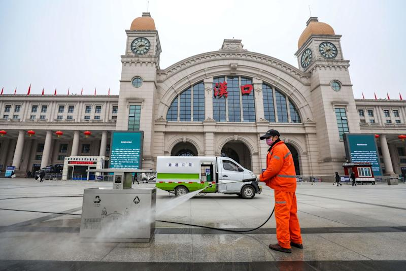 A cleaner washes the garbage bins outside the closed Hankou Railway Station in Wuhan. Source: Getty