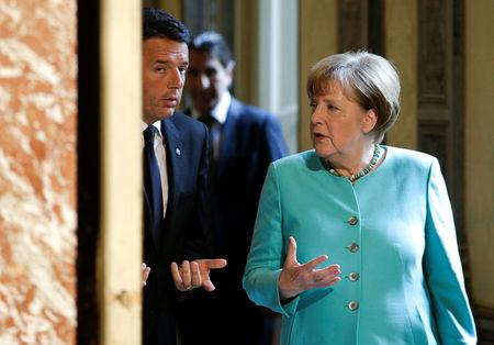 Italian Prime Minister Matteo Renzi (L) talks with German Chancellor Angela Merkel as they arrive for a news conference at Chigi Palace in Rome, Italy May 5, 2016. REUTERS/Max Rossi