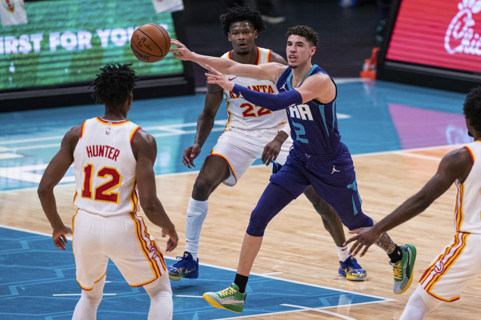 Charlotte Hornets guard LaMelo Ball (2) looks away while passing the ball past Atlanta Hawks forward De'Andre Hunter (12) and forward Cam Reddish (22) during the first half of an NBA basketball game in Charlotte, N.C., Saturday, Jan. 9, 2021. (AP Photo/Jacob Kupferman)