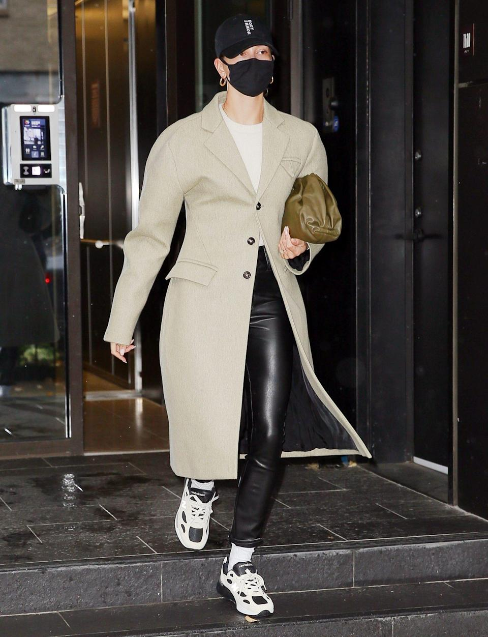 <p>Hailey Bieber steps out in a baseball cap, a long coat and sneakers on Monday morning to start her day in N.Y.C.</p>