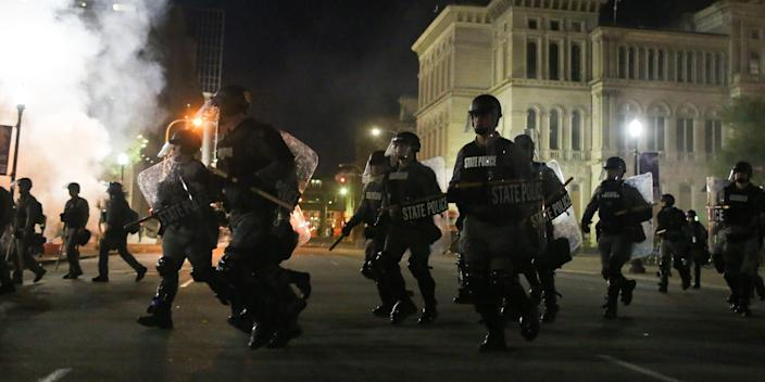 """Riot police run toward protesters after using smoke and stun grenades to clear Jefferson Square Park in Louisville, Kentucky on Wednesday. <p class=""""copyright"""">Daniel Shular</p>"""