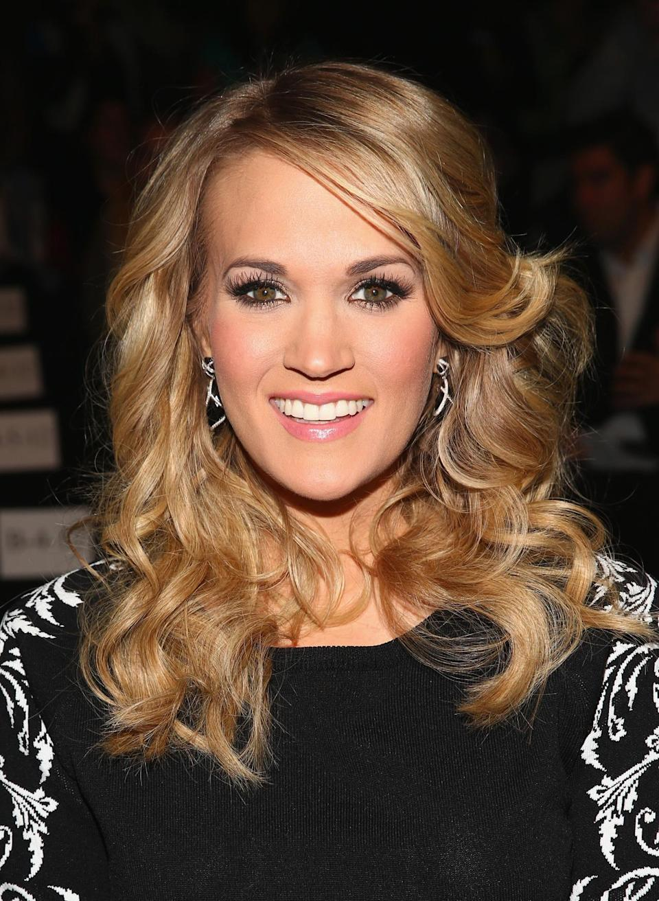 <p>Why mess with perfection? Carrie Underwood still rocks voluminous waves and pink-toned makeup. <i>(Photo: Getty Images)</i></p>