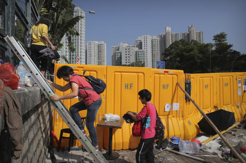People use a ladder to climb around barricades built by protesters at Hong Kong Baptist University in Hong Kong, Friday, Nov. 15, 2019. Protesters who have barricaded themselves in a Hong Kong university partially cleared a road they were blocking and demanded that the government commit to holding local elections on Nov. 24. (AP Photo/Kin Cheung)