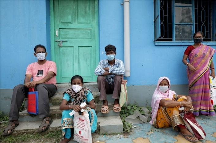 Locals wear protective face masks at government test center in Kolkata,