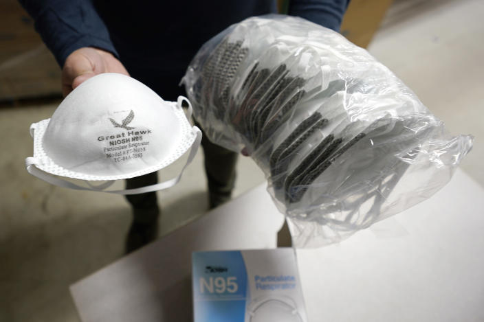 Ray Bellia holds up N95 personal protective masks, used by medical and law enforcement professionals, in the warehouse of his Body Armor Outlet store, Wednesday, Dec. 9, 2020, in Salem, N.H. Bellia's store rapidly evolved into one of the nation's 20 largest suppliers of personal protective equipment to states this past spring, according to a nationwide analysis of state purchasing data by The Associated Press. (AP Photo/Charles Krupa)
